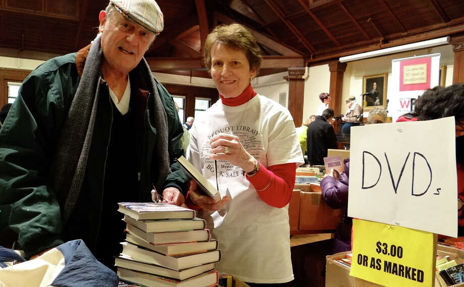 Pequot Library volunteer Lee Freeman assists Jack Grogins at Saturday's Mid-Winter Book Sale. Photo: Mike Lauterborn / Fairfield Citizen contributed