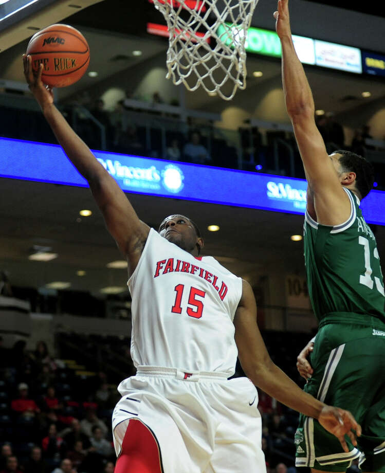 Fairfield University's Maurice Barrow lays up for two as Manhattan College's Emmy Andujar defends, during men's basketball action at the Webster Bank Arena in downtown Bridgeport, Conn. on Saturday January 18, 2014. Photo: Christian Abraham / Connecticut Post