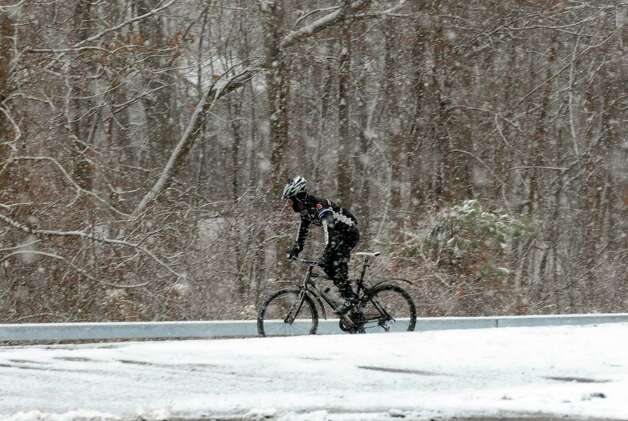 A cyclist braves a mid afternoon snow flurry along Route 140 on Saturday Jan. 18, 2014 in Bethlehem, N.Y.  (Michael P. Farrell/Times Union) Photo: Michael P. Farrell / 00025422A