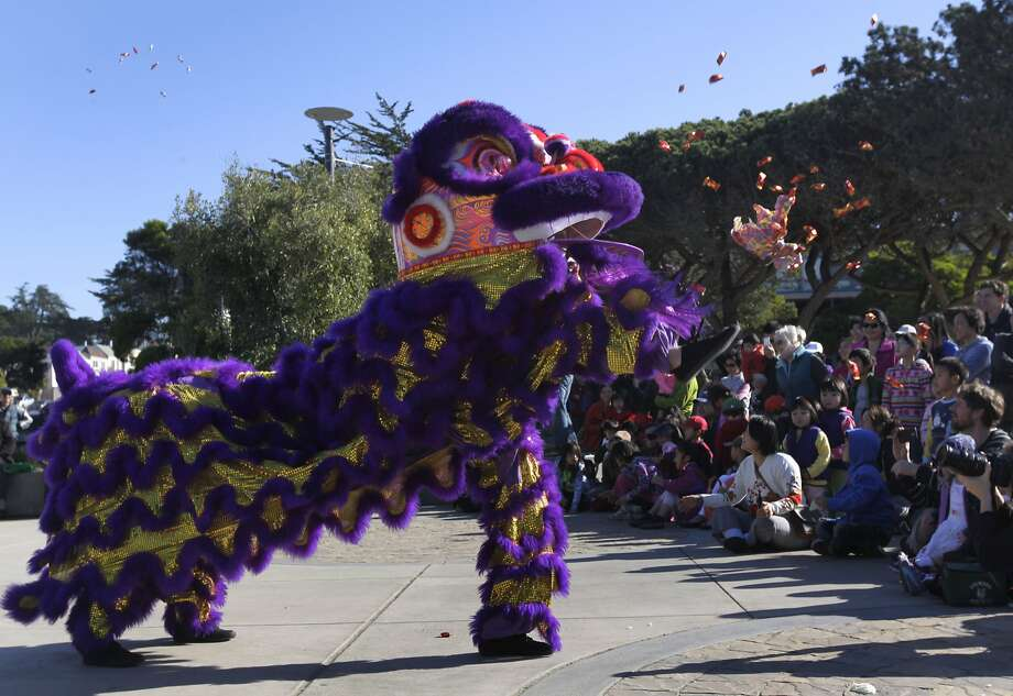 Liliana Yee and sister Adriana Yee launch candy into the air while  performing a lion dance at the Ortega branch library as the Year of the  Horse nears. Photo: Paul Chinn, The Chronicle