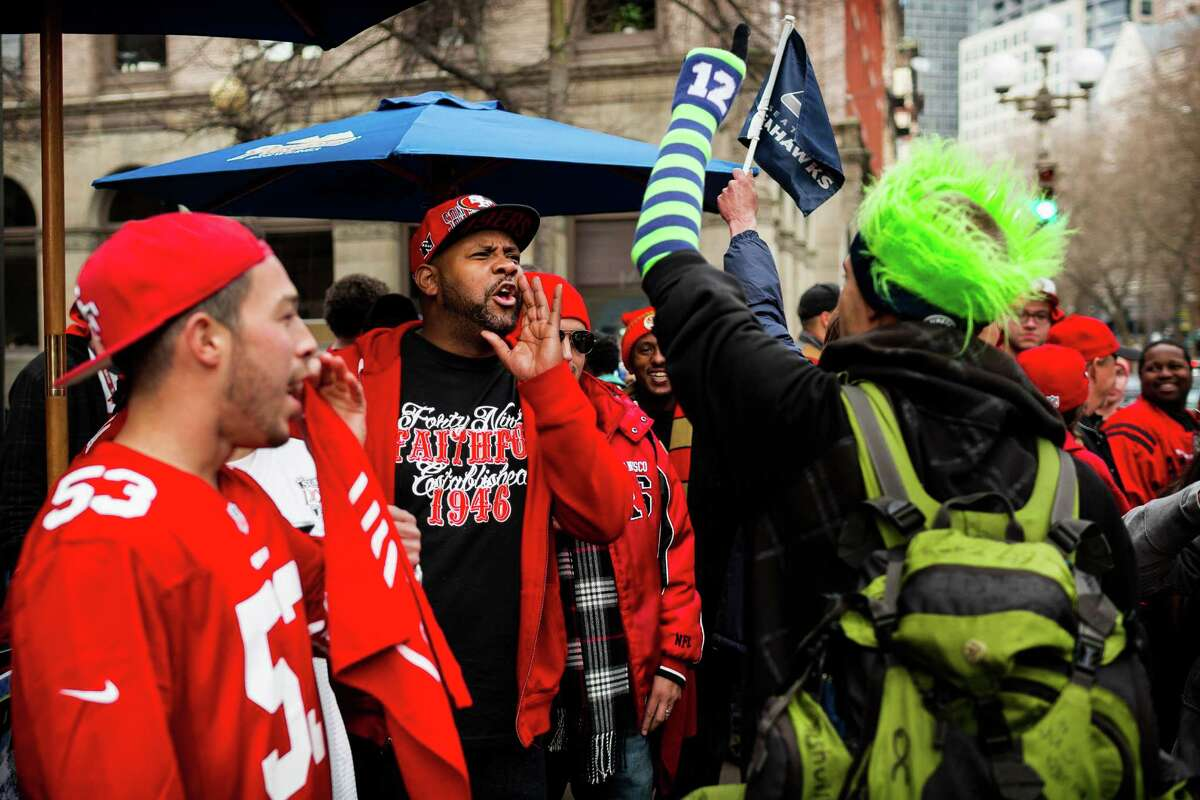 San Francisco 49ers fans playfully heckle a Seahawks fan during a rally outside of the J and M Cafe a day before the NFC Championship face-off against the Seattle Seahawks Saturday, Jan. 18, 2014, in Pioneer Square in Seattle. Police later showed up on the scene to keep the peace between rival fans.