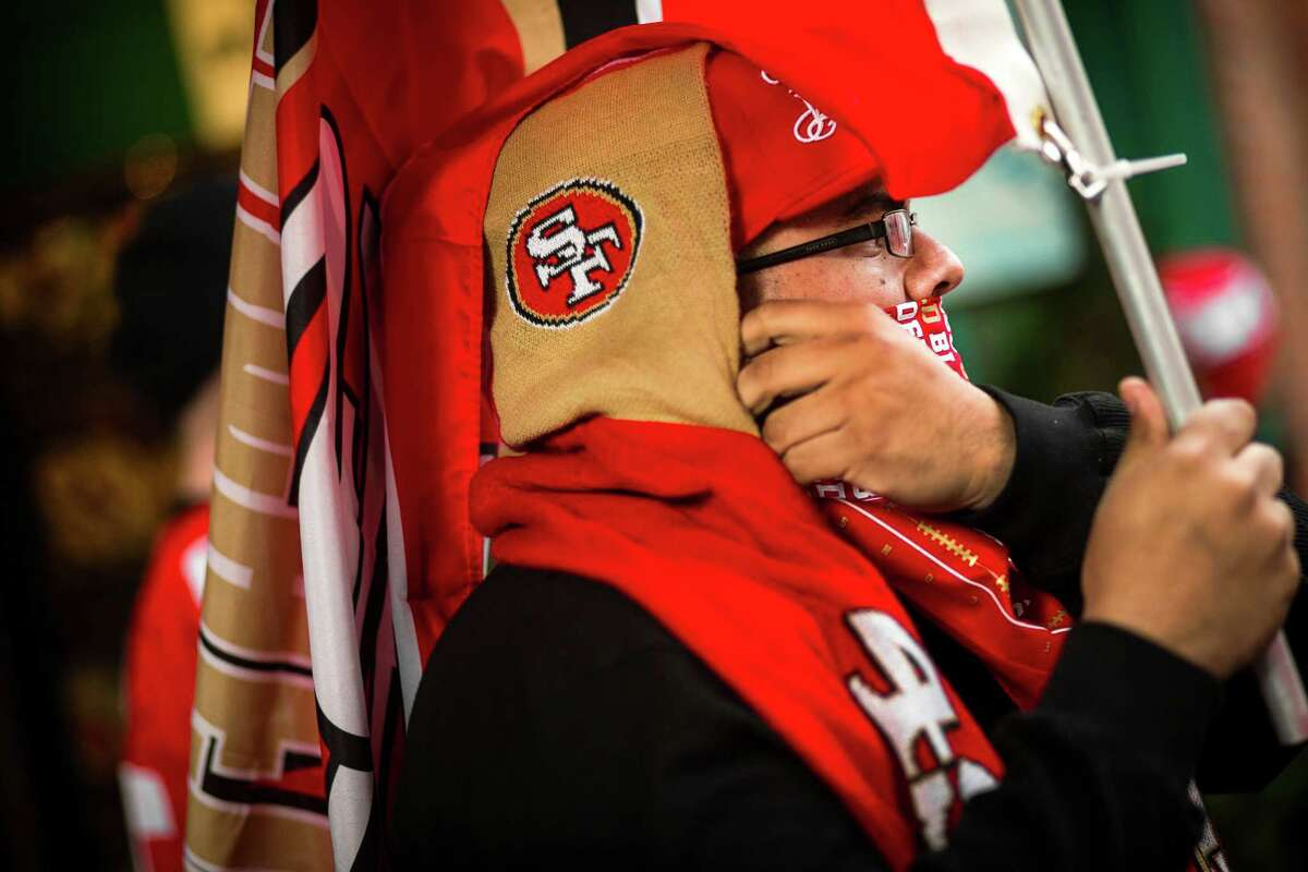 A decked-out, flag-bearing San Francisco 49ers fan rallies with dozens of others across four street corners outside of the J and M Cafe a day before the NFC Championship face-off against the Seattle Seahawks Saturday, Jan. 18, 2014, in Pioneer Square in Seattle. Police later showed up on the scene to keep the peace between rival fans.