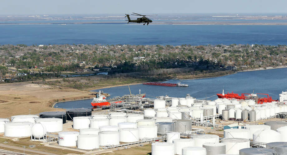 An AH-64D Apache Longbow flies over a refinery storage area along the Houston Ship Channel. Photo: Edward A. Ornelas, San Antonio Express-News / © 2014 San Antonio Express-News