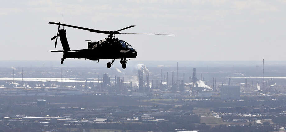An AH-64D Apache Longbow flies near a refinery along the Houston Ship Channel. Photo: Edward A. Ornelas, San Antonio Express-News / © 2014 San Antonio Express-News