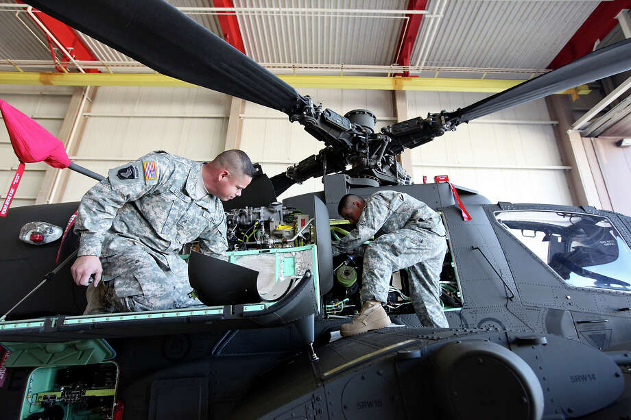 Texas Army National Guard Sgt. Raul Urbina, 33, (left) and Sgt. Luis Herrera, 25, work on the engine of an AH-64D Apache Longbow at Ellington Field Joint Reserve Base in Houston, Tx. Photo: Edward A. Ornelas, San Antonio Express-News / © 2014 San Antonio Express-News