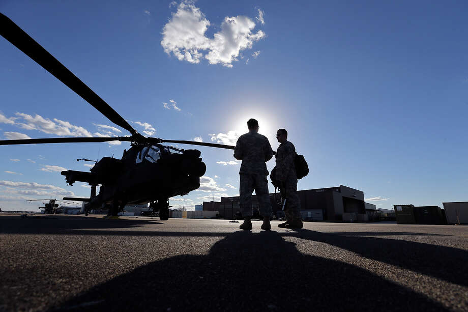 Texas Army National Guard Chief Warrant Officer 3 Dustin Mortenson, 29, (left) talks with Capt. Joseph Trevino, 34,  near an AH-64D Apache Longbow at Ellington Field Joint Reserve Base in Houston, Tx. Photo: Edward A. Ornelas, San Antonio Express-News / © 2014 San Antonio Express-News
