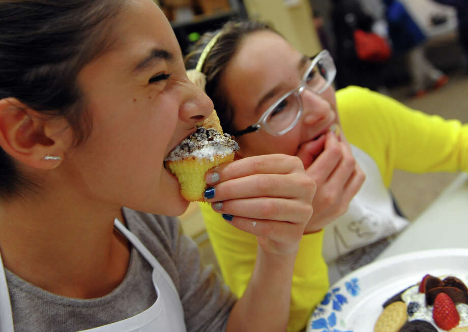 Caroline Rispoli, left, of Wilton, and her friend Anna Imrie, 11, both of Wilton, eat their desert creations after taking part in Westport READS: Teen Master Chef competition in the McManus Room at the Westport Library in Westport, Conn. on Saturday January 18, 2014. The event ties in with the Westport READ program's highlighting the life and work of master chef Julia Child. Photo: Christian Abraham / Connecticut Post