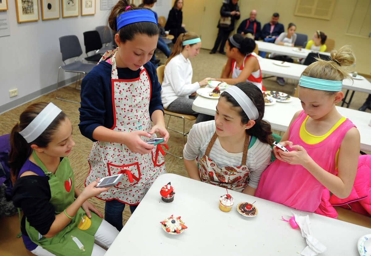 Ella Franzese, 11, left, and her friends Roxy Augeri, 11, Caroline Vandis, 11, and Annie Bowens, 11, at right, snap pictures of their desert creations after taking part in Westport READS: Teen Master Chef competition in the McManus Room at the Westport Library in Westport, Conn. on Saturday January 18, 2014. The kids got to create their own desert and compete for best cupcake, best use of ingrediants, and best presentation. The event ties in with the Westport READ program's highlighting the life and work of master chef Julia Child.