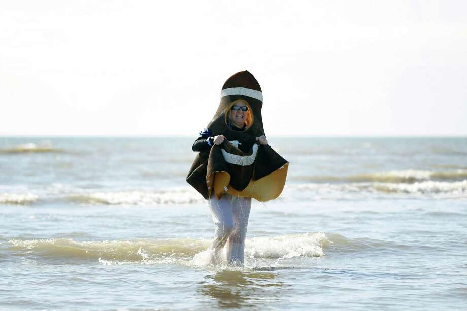Plunger Marilyn Holler, dressed as a football and laughing, waddles out of the water, during the 2014 Polar Plunge, Saturday, January 18, 2014 on Stewart Beach in Galveston, Texas. The annual event, hosted by the Special Olympics, raises money for Gulf Coast special athletes. Photo: Todd Spoth, For The Chronicle / © TODD SPOTH, 2014