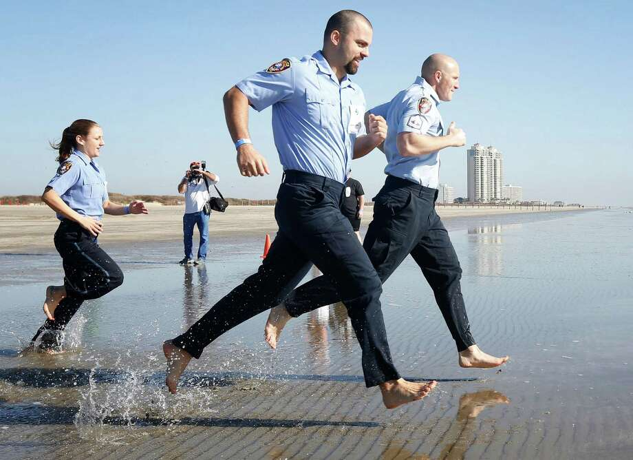 Members of a team from a local EMS crew enter the water during the 2014 Polar Plunge, Saturday, January 18, 2014 on Stewart Beach in Galveston, Texas. The annual event, hosted by the Special Olympics, raises money for Gulf Coast special athletes. Photo: Todd Spoth, For The Chronicle / © TODD SPOTH, 2014