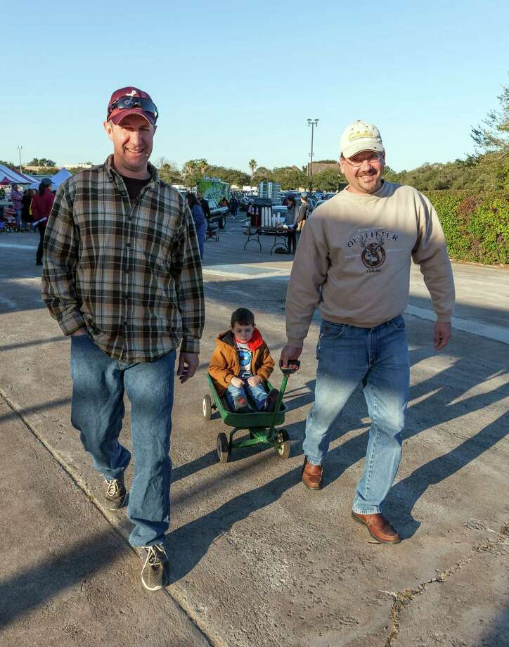 Matt Bolinger, 4-year-old Levi Bolinger and Brandon Buell arrive a half hour before opening time. Photo: Craig Hartley, For The Chronicle / Copyright: Craig H. Hartley