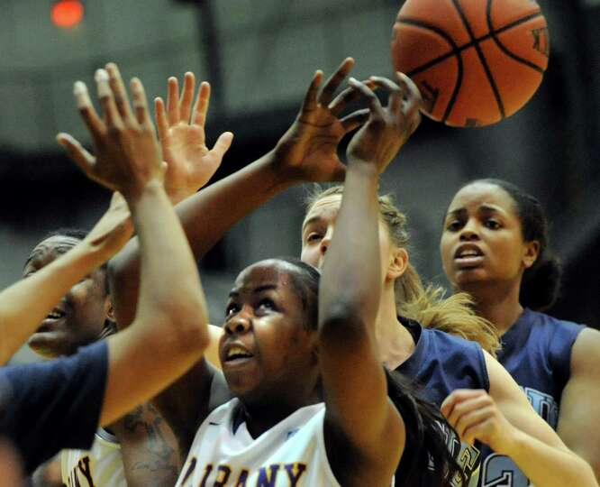 UAlbany's Imani Tate, center, battles for a loose ball during their basketball game against Maine on