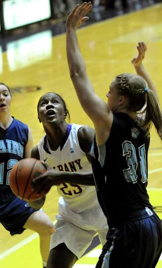 UAlbany's Shereesha Richards, center, shoots for the hoop as Maine's Liz Wood defends during their b