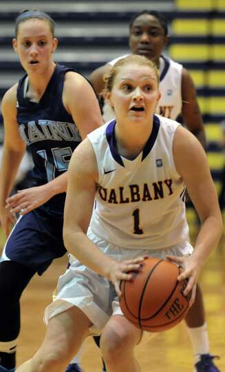 UAlbany's Erin Coughlin, center, controls the ball during their basketball game against Maine on Sat