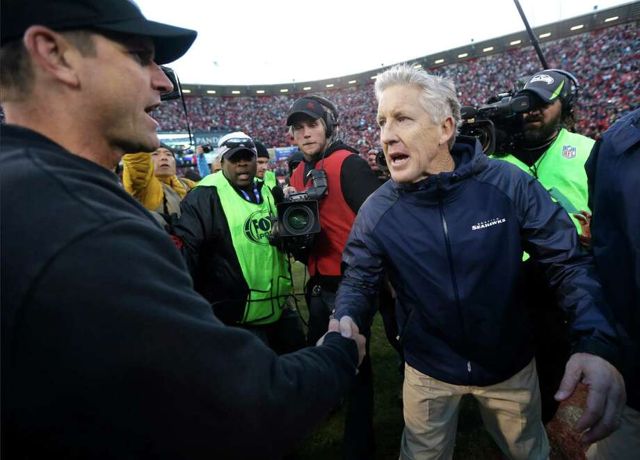 Beyond their intense NFC West rivalry, 49ers coach Jim Harbaugh, left, and his Seahawks counterpart, Pete Carroll, are longtime adversaries dating to their Pac-10 days at Stanford and Southern Cal, respectively. Photo: Marcio Jose Sanchez, STF / AP