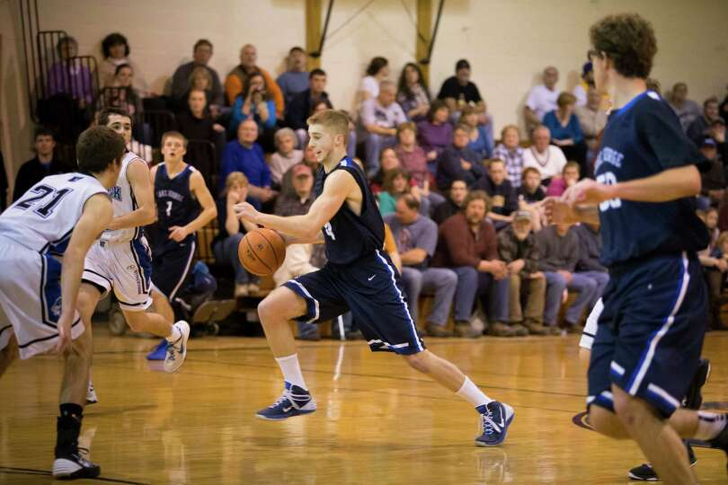 Lake George's #4 Joel Wincowski drives the ball down the court during the boys' basketball game agai