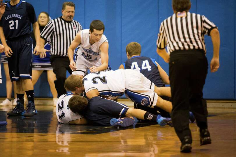 Lake George and Hoosick Falls players pile up, fighting for possession of the ball during the boys'
