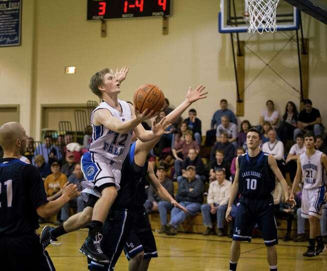 Hoosick Falls' #12 Will Bradley takes the ball to the hoop during the boys' basketball game against