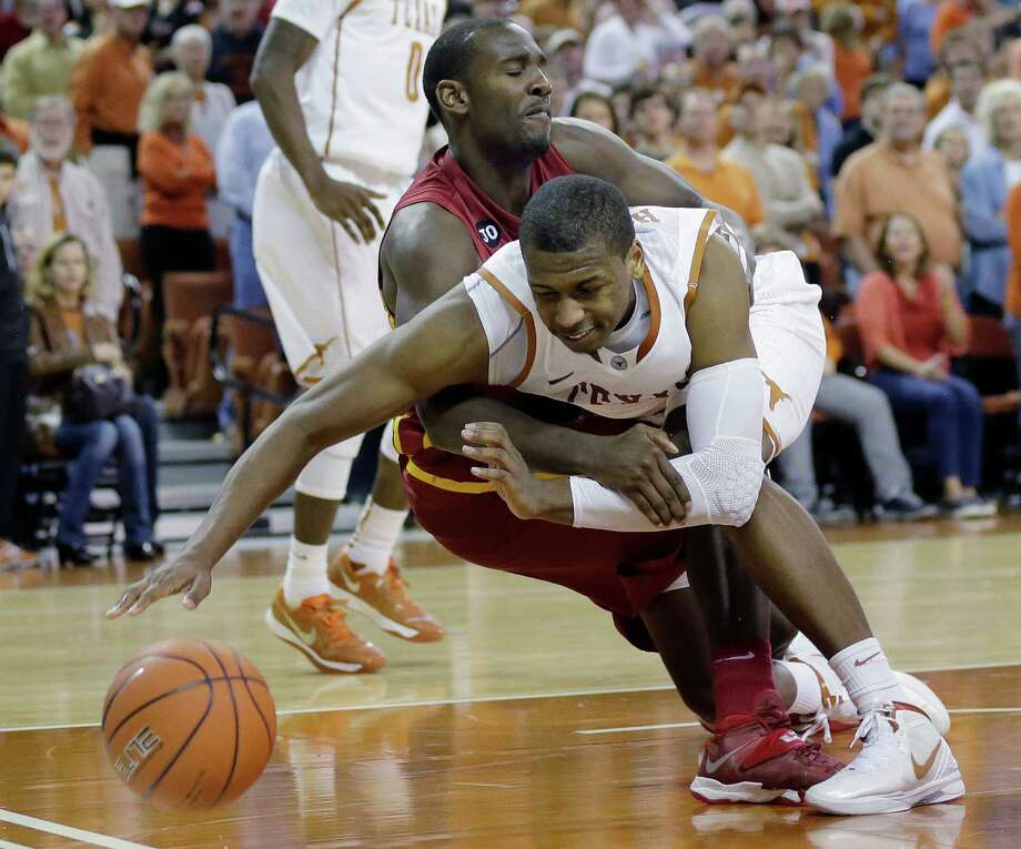 Texas' Jonathan Holmes, front, and Iowa State's Dustin Hogue, back, fall as they chase a loose rebound during the second half on an NCAA college basketball game, Saturday,  Jan. 18, 2014, in Austin, Texas. Texas won 86-76. (AP Photo/Eric Gay) Photo: Eric Gay, Associated Press / AP
