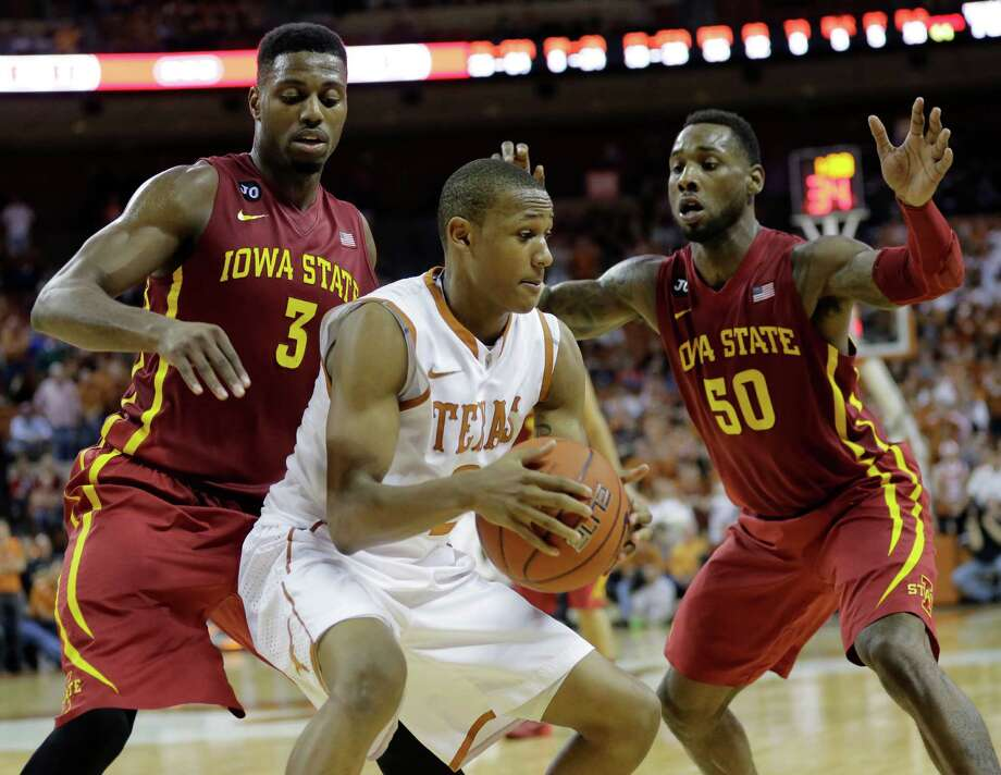 Texas' Demarcus Holland, center, is pressured by Iowa State's Melvin Ejim (3) and DeAndre Kane (50) during the second half on an NCAA college basketball game, Saturday,  Jan. 18, 2014, in Austin, Texas. (AP Photo/Eric Gay) Photo: Eric Gay, Associated Press / AP