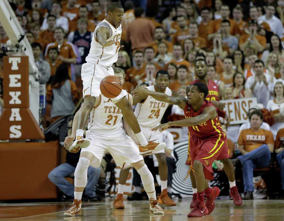 Iowa State's Monte Morris (11) passes the ball around Texas defenders Demarcus Holland (2) and Connor Lammert (21) during the first half on an NCAA college basketball game, Saturday,  Jan. 18, 2014, in Austin, Texas. (AP Photo/Eric Gay) Photo: Eric Gay, Associated Press / AP