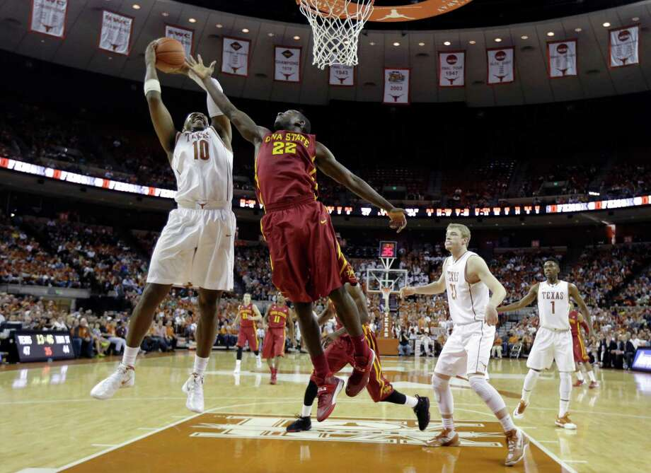 Texas' Jonathan Holmes (10) grabs a rebound in front of Iowa State's Dustin Hogue (22) during the second half on an NCAA college basketball game, Saturday, Jan. 18, 2014, in Austin, Texas. Texas won 86-76. (AP Photo/Eric Gay) Photo: Eric Gay, Associated Press / AP