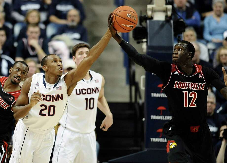 Connecticut's Lasan Kromah (20) and Louisville's Mangok Mathiang (12) reach for a loose ball during the first half of an NCAA college basketball game, Saturday, Jan. 18, 2014, in Storrs, Conn. Photo: Jessica Hill, AP / Associated Press