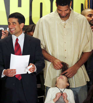 Nicholas LaHood, who is running for district attorney, (left) waits to speak as Spurs' Tim Duncan jokes with LaHood's daughter Maya, 5, Saturday Jan. 18, 2014 at the St. Paul Community Center. Photo: San Antonio Express-News / © 2014 San Antonio Express-News