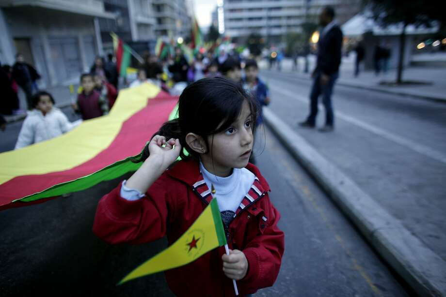 CAPTION CORRECTS DATE FROM 2013 TO 2014 -  A girl holds a Kurdish flag during a protest in Athens on Saturday, Jan. 18 2014. Several hundred Kurds marched through central Athens Saturday to demand an independent state. The march was one of several staged worldwide by the Kurdish Supreme Council to ask that the Kurdish question be on the agenda of the upcoming Geneva II Middle East Peace Conference on the Syrian conflict. An estimated 26-33 million Kurds inhabit a region known as Kurdistan, which includes adjacent parts of Turkey, Iran, Iraq and Syria. (AP Photo/Kostas Tsironis) Photo: Kostas Tsironis, Associated Press