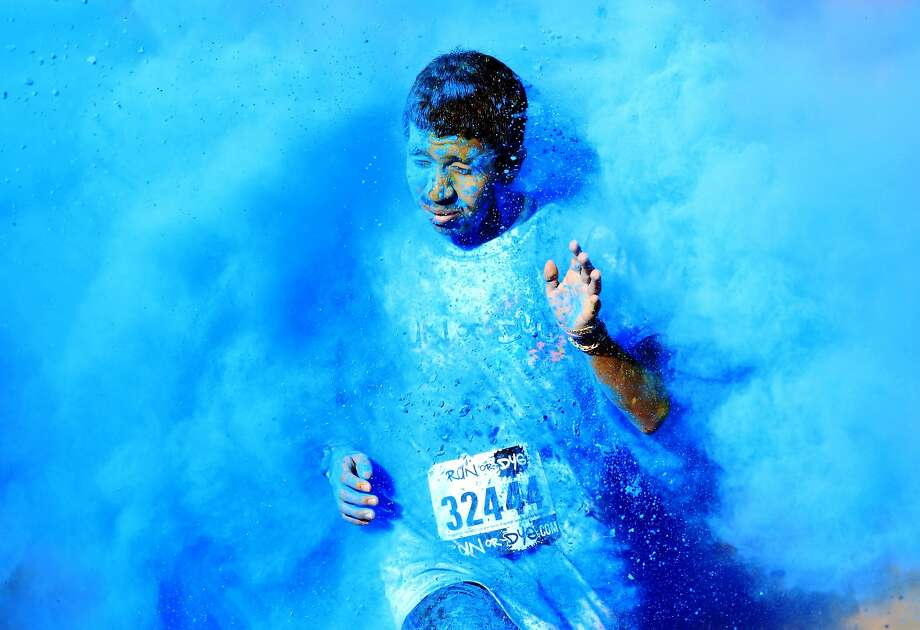 A participant gets blasted with blue dye during the Run or Dye 5k Saturday Jan. 18, 2014 at the McAllen Convention Center in McAllen, Texas. Participants ran 3.1 miles and had the chance to get painted with different color of dyes made out of corn starch. (AP Photo/The Monitor, Gabe Hernandez) Photo: Gabe Hernandez, Associated Press