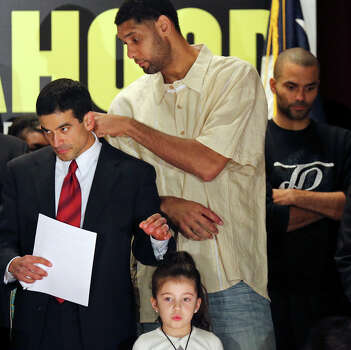 Nicholas LaHood, who is running for district attorney, (left) has his collar adjusted by Spurs' Tim Duncan while waiting to speak Saturday Jan. 18, 2014 at the St. Paul Community Center. Pictured on stage with LaHood are his daughter Maya, 5, (bottom) and Spurs' Tony Parker (right). Photo: Edward A. Ornelas, San Antonio Express-News / © 2014 San Antonio Express-News