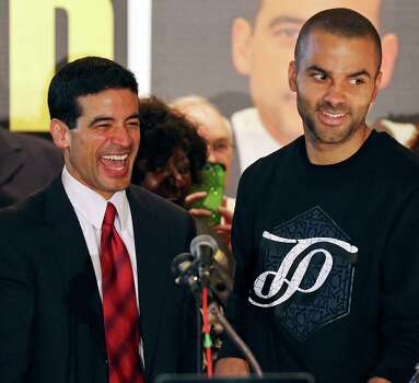 Nicholas LaHood, who is running for district attorney, (left) jokes with Spurs' Tony Parker Saturday Jan. 18, 2014 at the St. Paul Community Center. Photo: Edward A. Ornelas, San Antonio Express-News / © 2014 San Antonio Express-News