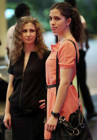 """Russian punk band Pussy Riot members Nadezhda Tolokonnikova, right, and Maria Alekhina arrive on Saturday, Jan. 18, 2014 for the Prudential Eye Awards in Singapore. They were in the city-state to attend the inaugural Prudential Eye  Awards along with other international artists, where they were nominated  for an award in the digital/video category for their performances,  including the """"punk prayer."""" That's the video that got them arrested and  jailed. The members have all been released now. The video didn't win. Photo: Wong Maye-E, AP  / AP2014"""