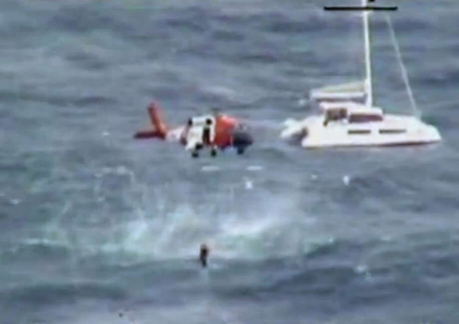 In this image from video provided by the U.S. Coast Guard a Coast Guard helicopter crew hoists one of four people from the 42-foot sailboat Be Good Too, background, about 300 miles off Virginia's coast Tuesday Jan. 14, 2014. Be Good Too was headed to the British Virgin Islands from New York when the crew contacted the Coast Guard on Monday. The Coast Guard says the crew reported that the sailboat was disabled and adrift. The sailboat's crew was rescued around 9:15 a.m. Tuesday. Photo: AP  / US Coast Guard