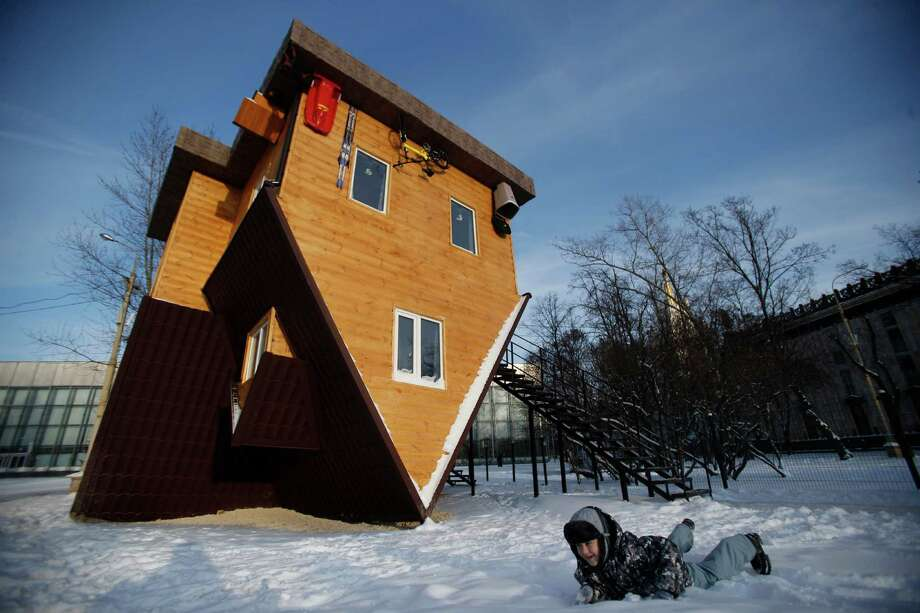 A boy plays in snow in front of the Upside Down House at the All-Russia Exhibiton Center in in Moscow, Russia, Friday, Jan. 17, 2014. Its creators say the interior can cause dizziness. Photo: Pavel Golovkin, AP  / AP2014