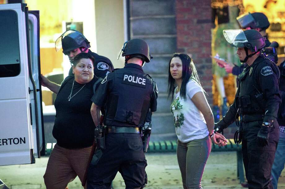 Two women are arrested in Downtown Fullerton, Calif.,  on Saturday, Jan. 18, 2014. They were protesting the acquittal of two former California police officers in the beating death of a homeless man.  (AP Photo/The Orange County Register, Kyusung Gong)  Photo: KYUSUNG GONG,, AP  / The Orange County Register