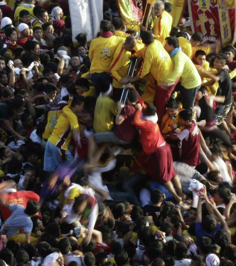 Filipino Catholic devotees climb a carriage to touch and kiss the image of the Black Nazarene in annual procession to celebrate its feast day Thursday, Jan. 9, 2014 in Manila, Philippines. Hundreds of thousands of Filipino Catholics began a raucous religious procession in Manila Thursday to honor a centuries-old black statue of Jesus Christ in an annual event that organizers say was being held partly to pray for the victims of a monster typhoon that devastated the central Philippines last year. Photo: Bullit Marquez, AP  / AP