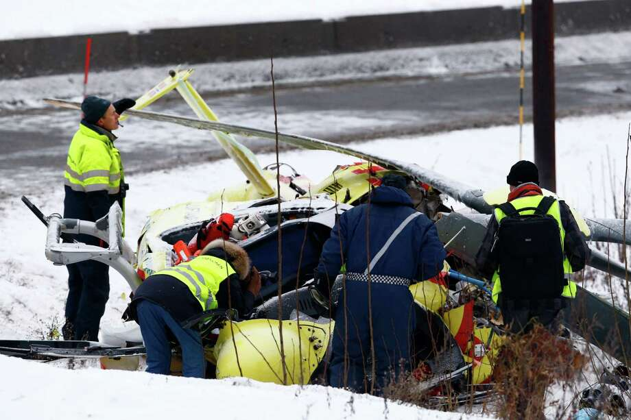 Rescuers attend the site of a helicopter crash in which two crew members were killed and one injured whilst attempting to attend at the site of a car accident in Sollihoegda, Norway, some 30 kilometers southwest of Oslo, Tuesday, Jan. 14, 2014. (AP Photo/NTB Scanpix, Heiko Junge)  Photo: Heiko Junge, AP  / NTB scanpix