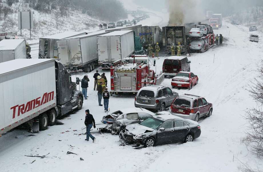 Firefighters and police respond following a multiple-vehicle accident in the northbound lane of I-65 just north of Eisenhower Road  Saturday, Jan. 18, 2014, in Lafayette, Ind. A box truck caught fire in the accident. Numerous slide offs also took place in the immediate area and traffic in both lanes backed up heavily. Photo: John Terhune, AP  / Journal & Courier