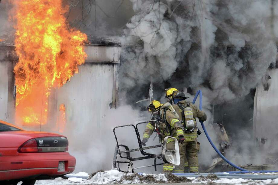 Volunteer firefighters approach a fully-engulfed trailer fire Wednesday, Jan. 15, 2014, at Deerwood Mobile Home Court in Marion, Ind. Three puppies died in the blaze. Photo: JEFF MOREHEAD, AP  / AP2014