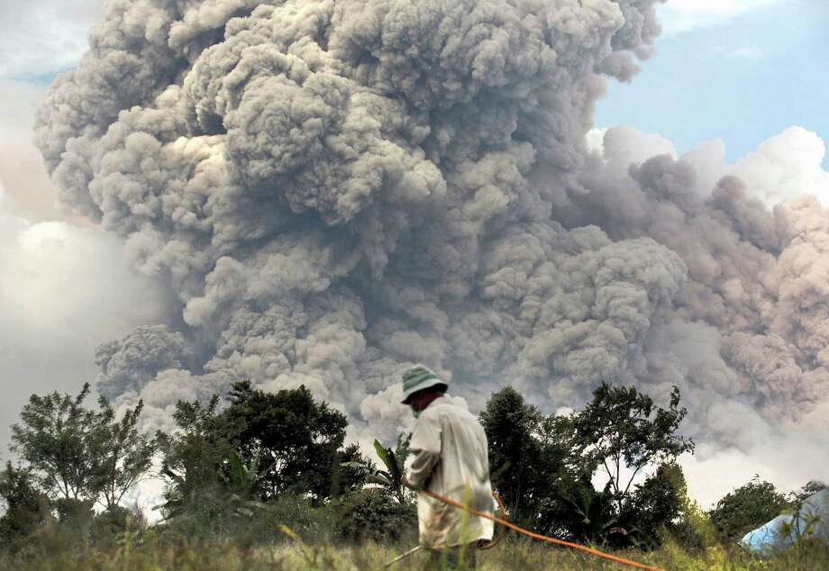 A farmer works on a field as Mount Sinabung erupts in Perteguhan, North Sumatra, Indonesia, Tuesday, Jan. 14, 2014. The volcano has sporadically erupted since September, forcing thousands of people who live around it slopes to flee their homes. Photo: Binsar Bakkara, AP  / AP2014