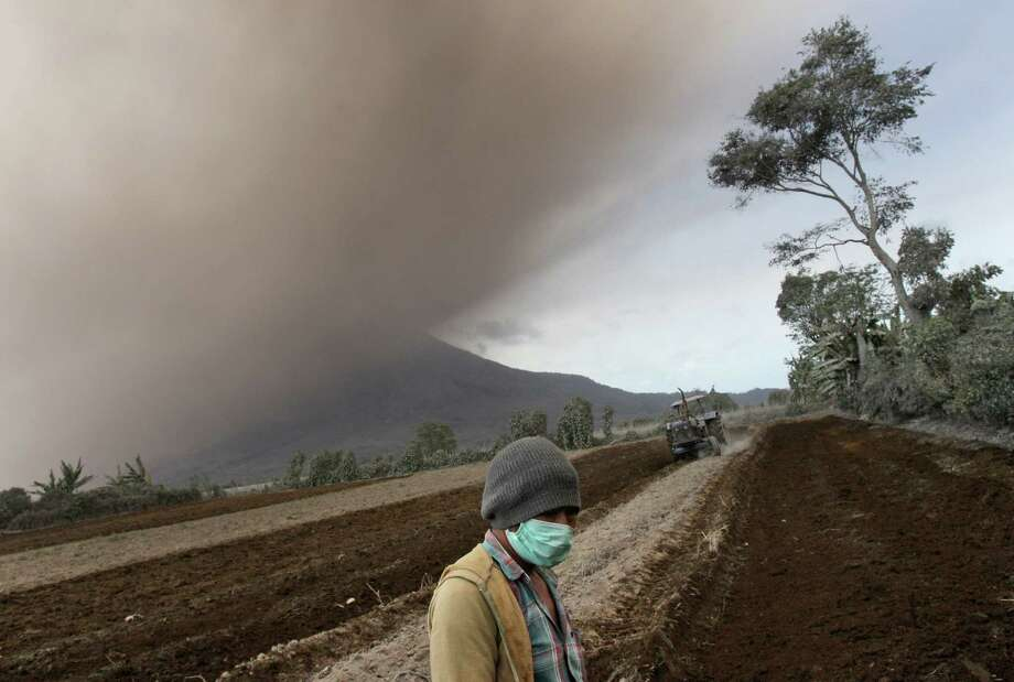 A worker pauses as Mount Sinabung spews volcanic ash during an eruption on a field in Kuta Tonggal, North Sumatra, Indonesia, Thursday, Jan. 16, 2014. More than 20,000 people have been evacuated from villages around the crater of Mount Sinabung into several temporary shelters since authorities raised the alert status for the rumbling volcano to the highest level in November. Photo: Binsar Bakkara, AP  / AP2014