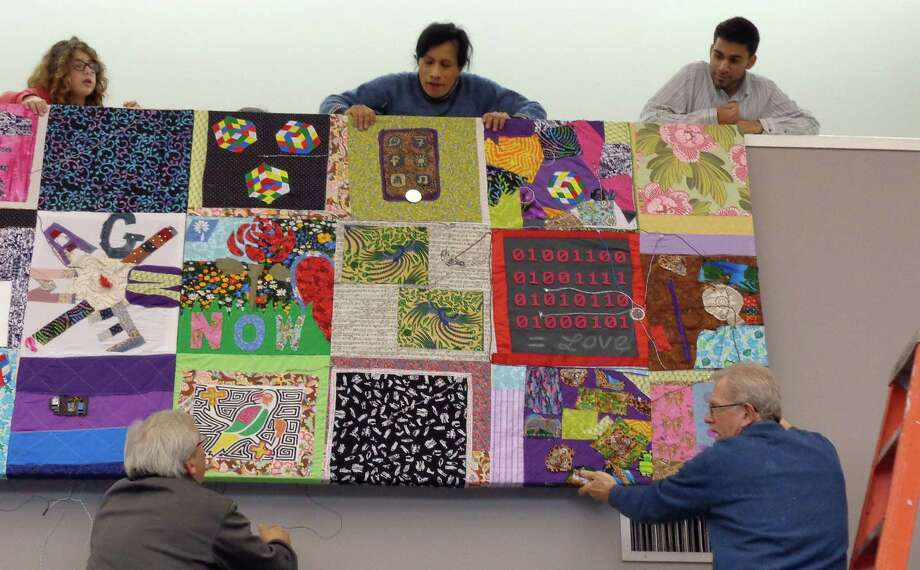 Balam Soto, center above, the Westport Library's maker-in-residence, is joined by others involved in the digital quilt-making project to install the quilt Saturday. Photo: Meg Barone / Westport News contributed