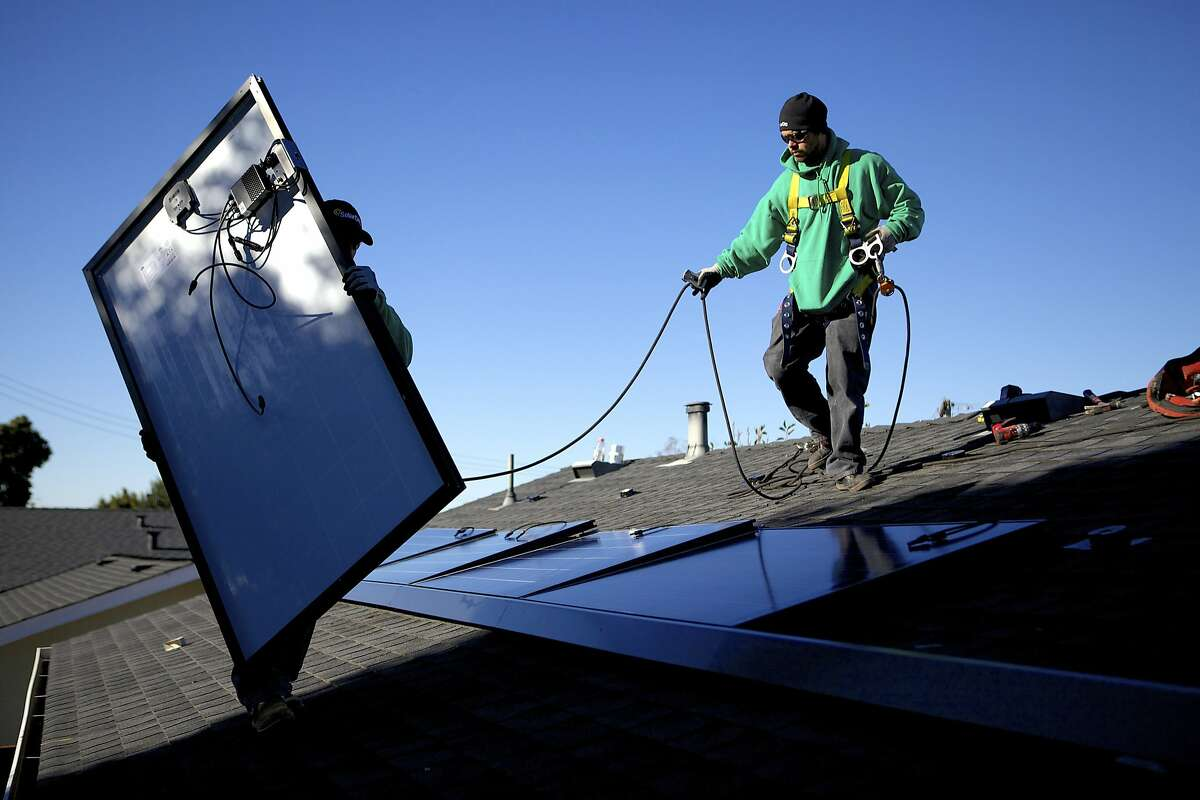 SolarCity employees Luis Zavala, left, and Jose Gazo install photovoltaic panels on the roof of a house in San Leandro, Calif., Dec. 9, 2013. The company, which is the nation's largest provider of rooftop solar energy with more than 80,000 customers, has not made a dime but its share price has soared more than 500 percent in the past year. (Thor Swift/The New York Times)