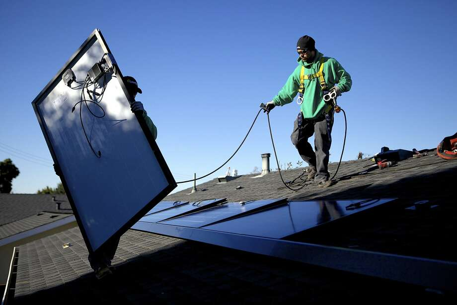 SolarCity employees Luis Zavala (left) and Jose Gazo install photovoltaic panels on the roof of a house in San Leandro last month. Photo: Thor Swift, New York Times