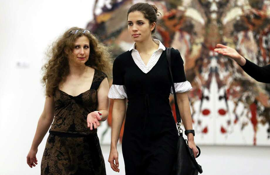 Russian punk band Pussy Riot members Nadezhda Tolokonnikova, right, and Maria Alekhina, left, arrive, Friday, Jan. 17, 2014, for a press conference at the Prudential Eye Awards Art Exhibition preview in Singapore. The band members were in the city-state to attend the inaugural 