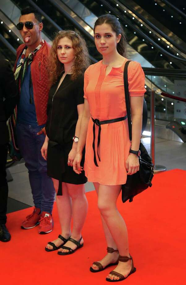 "Russian punk band Pussy Riot members Nadezhda Tolokonnikova, right, and Maria Alekhina pose with Australian artist Eric Bridgeman, left, as they arrive on Saturday, Jan. 18, 2014 for the Prudential Eye Awards in Singapore. They are in the city-state to attend the inaugural Prudential Eye Awards along with other international artists, where they have been nominated for an award in the digital/video category for their performances, including the ""Punk Prayer."" Photo: Wong Maye-E, AP  / AP2014"