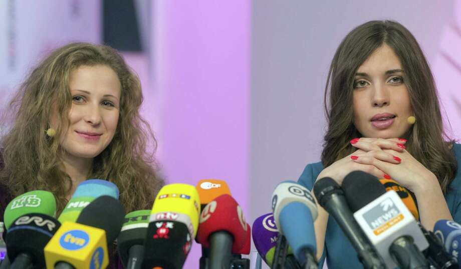 Two members of Russian punk group Pussy Riot, Nadezhda Tolokonnikova (R) and Maria Alyokhina (L), answer journalists' questions during their news conference in Moscow on December 27, 2013. A freed member of the Pussy Riot punk band said Friday the rockers still wanted Russian President Vladimir Putin out of power, adding she would like freed ex-tycoon Mikhail Khodorkovsky to stand in elections and replace him. AFP PHOTO/YEVGENY FELDMAN Photo: AFP, Getty Images / 2013 AFP