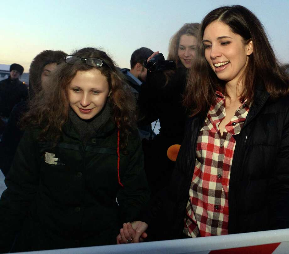 Two members of anti-Kremlin punk band Pussy Riot, Nadezhda Tolokonnikova (R) and Maria Alyokhina smile as they meet in the airport of the Siberian city of Krasnoyarsk, some 3500 km (2174 miles) east of Moscow, on December 24, 2013. The two jailed members of anti-Kremlin punk band Pussy Riot, whose imprisonment prompted a wave of global outrage, walked free yesterday and immediately vowed to fight injustice in Russian prisons. AFP PHOTO/VASILY MAXIMOV Photo: AFP, Getty Images / 2013 AFP