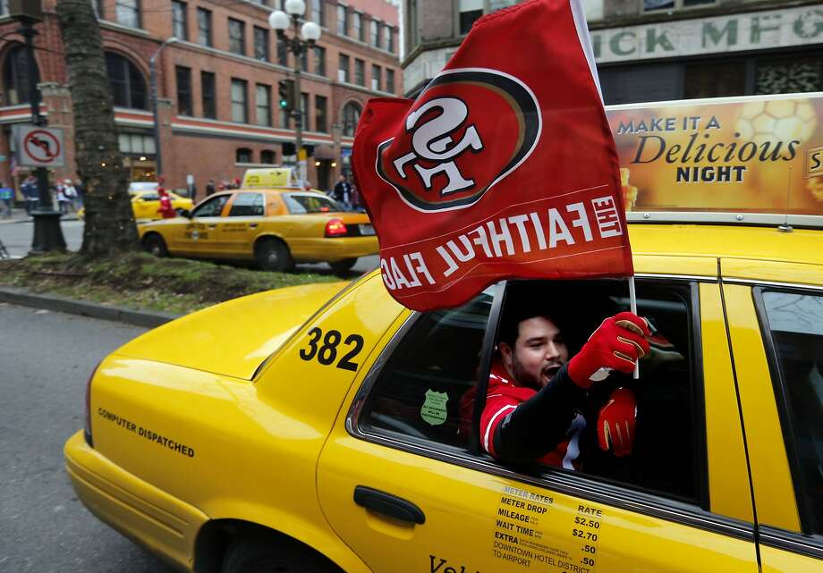 All's fare in a rivalry game: A 49ers fan cabs it through downtown Seattle waving his flag before the 49ers lost to the Seahawks in the NFC Championship Game. Photo: Michael Macor, The Chronicle